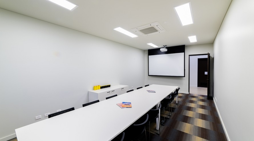 Photo of meeting room one showing board room layout and projector screen