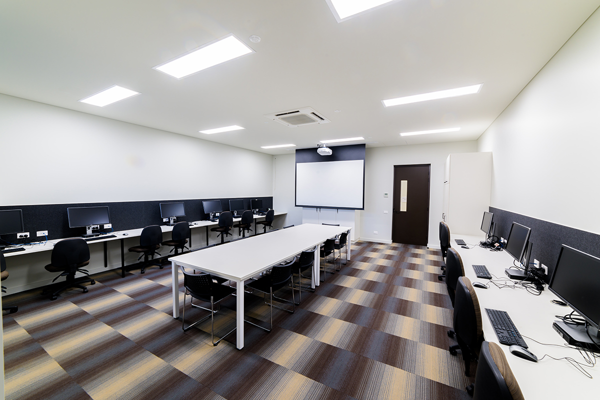 Image of Learning Lab One showing computers, desks and projector screen