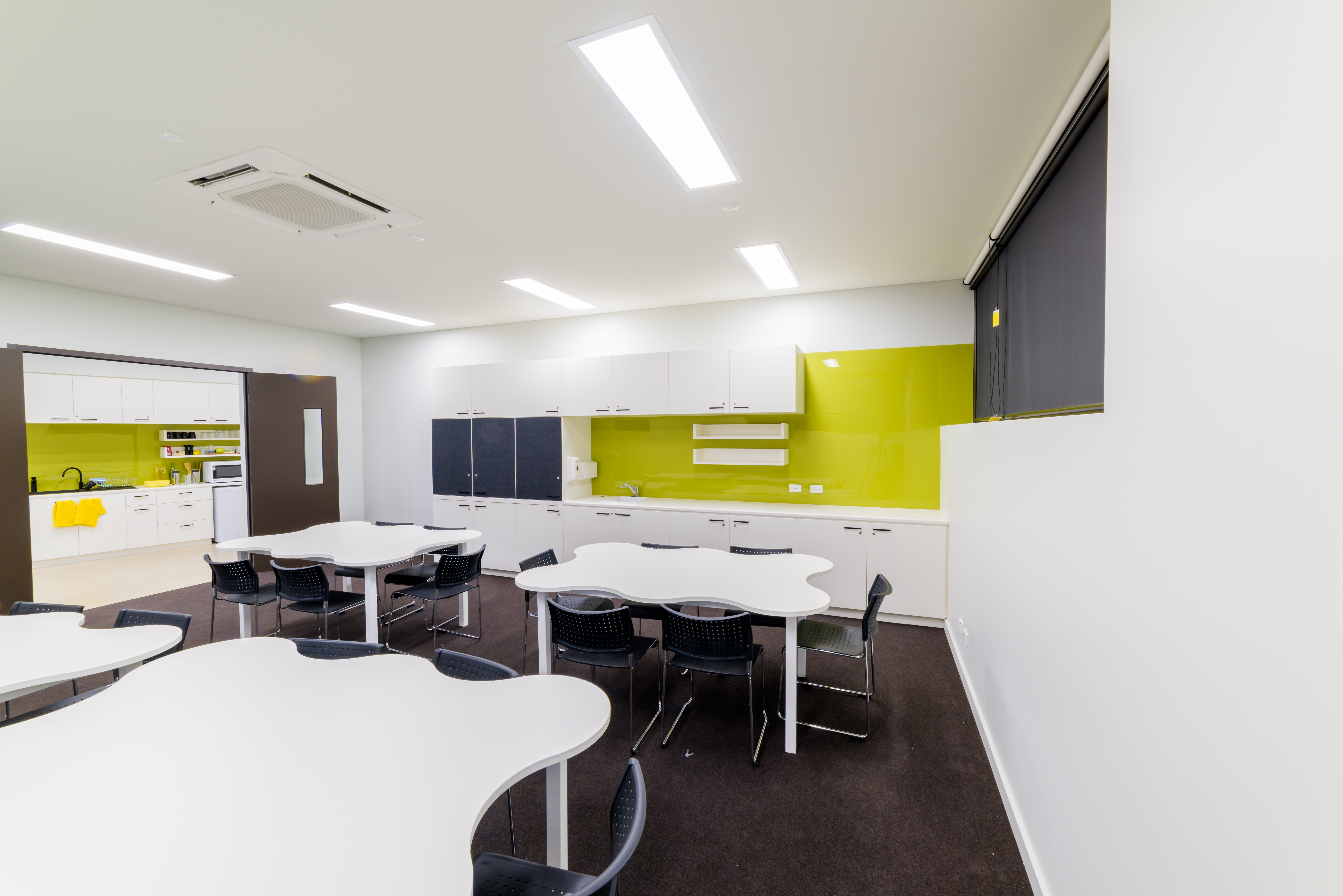 Photo of Activity Room two with tables and chairs and corridor kitchenette in the background
