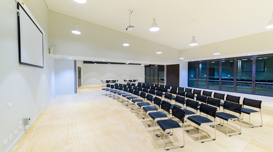 Image of full multipurpose room configured for a conference and with meeting tables at the back