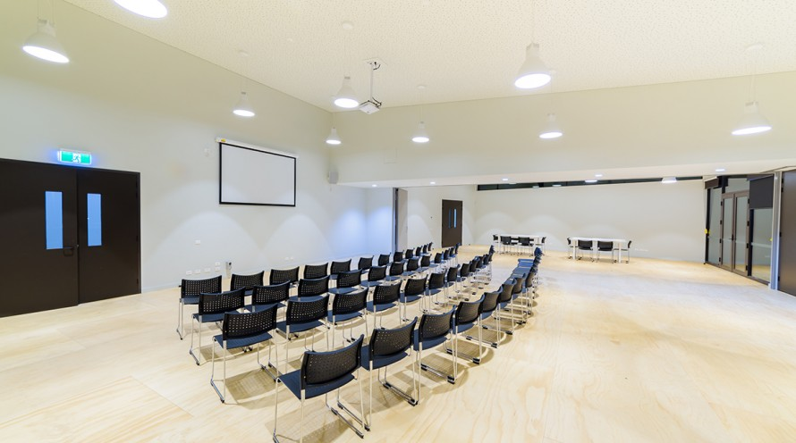 Photo of full multipurpose room configured for a conference and highlighting projector screen