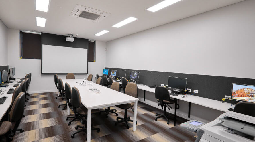 Room with projector, computers, desks and chairs