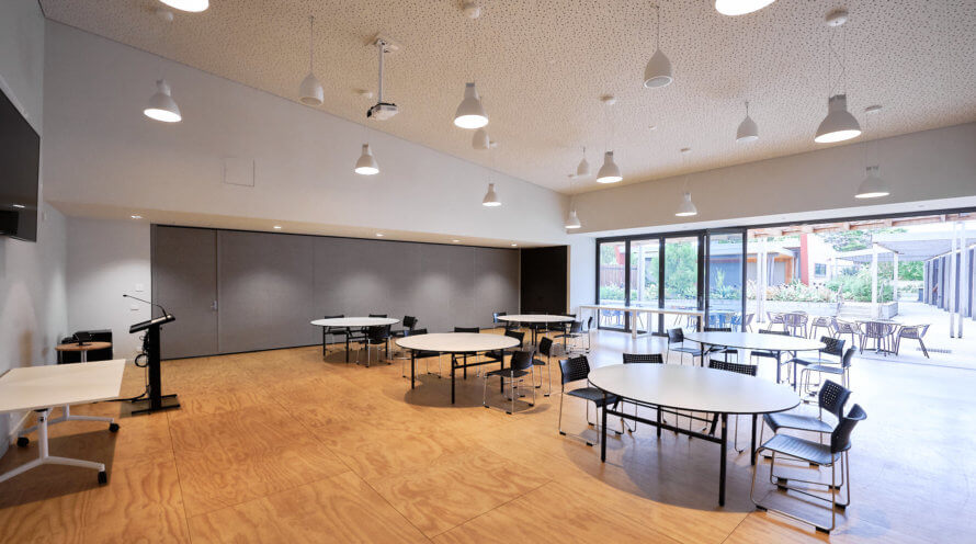 big room with tables, chairs and doors out to courtyard