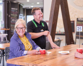 Older woman sitting at table with coffee with waiter next to her