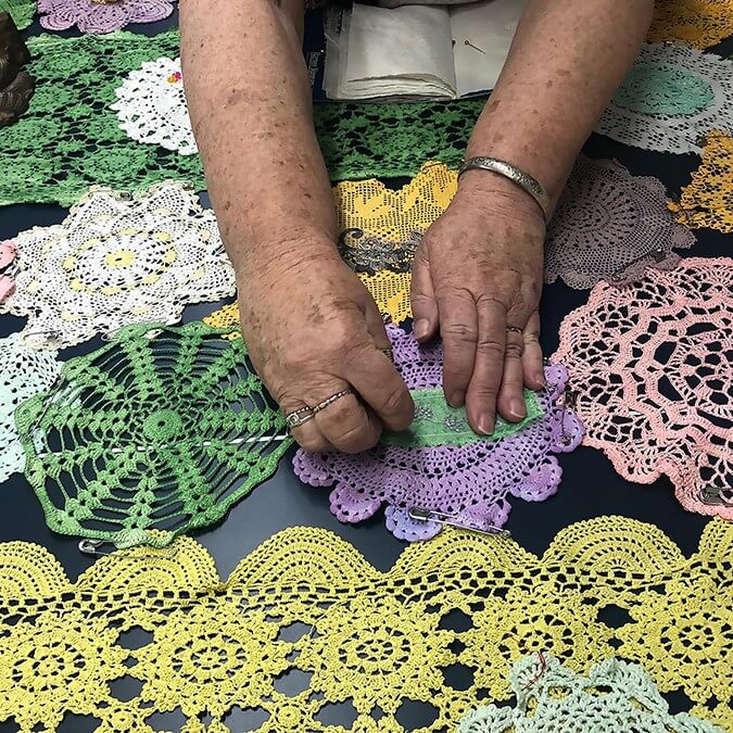 hands stitching doilies together
